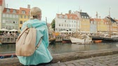 denmark : A woman sits on the embankment and admires the colorful buildings on the banks of the Nyhavn canal in Copenhagen Stock Footage