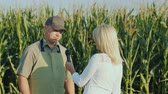 mikrofon : A journalist interviews a successful farmer. Stand in the background of a field of corn