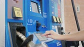 inserting : Woman pays for refueling a car with a credit card in a column at a gas station