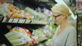 bakkaliye : Woman chooses fresh vegetables in the organic department of the supermarket
