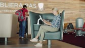 frança : Paris, France, Charles de Gaulle Airport, September 2018: A woman uses a terminal for entertainment, sits in a comfortable chair. Airport facilities and service Stock Footage