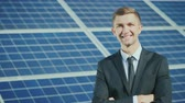 electronics industry : Portrait of a successful businessman, smiling and looking at the camera. It stands on the background of solar panels Stock Footage