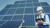настройка : A young businessman in a white helmet uses a tablet on the background of solar panels