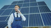 настройка : Young engineer speaks on the phone on the background of large solar panels