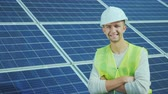 szolárium : Portrait of a worker in overalls and a helmet on the background of solar panels. Smiles, looks into the camera Stock mozgókép