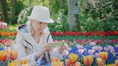 flowerbeds : A blonde in a light hat makes a photo on the phone surrounded by colorful tulips in the city park