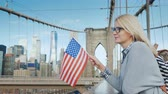 американский флаг : A woman with the flag of America in her hand stands on the Brooklyn Bridge with a view of Manhattan. Tourism in the USA