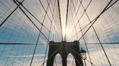 first person view : Famous Brooklyn Bridge. The sun high in the sky will light above the pillars of the bridge. Symbol of New York City Stock Footage