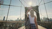 blogger : Woman talking on video chat on the Brooklyn Bridge. He looks at the camera of the smartphone, waves his hand. Traveling in New York and USA