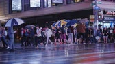 obter : New York, USA, October 2018: A crowd of pedestrians with umbrellas in their hands in a hurry to cross the street in a busy area of Manhattan