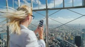 фехтование : Tourist photographs a beautiful view of the city of New York. It stands at the fence of the observation platform of a skyscraper. Traveling in the USA and New York