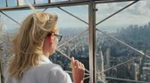 esgrima : A woman looks down at a beautiful view of the business district of Manhattan. It stands at the fence of the observation platform of a skyscraper Vídeos