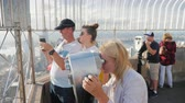 imparatorluk : New York, USA, October 2018: A group of visitors at the viewing platform, Empire State Building. They look through binoculars, take photos against the background of the city Stok Video