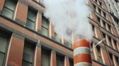 smoke stack : Steam comes from the striped pipe, against the background of tall brick buildings. Typical view of the street of New York