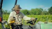 farming equipment : A farmer in a big hat works on a small tractor near the vineyard. Stock Footage