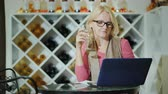 blogger : Woman tasting wine, sitting at a table in a winery, using a laptop