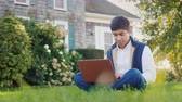 пользователь : A young man of Indian nationality enjoys a laptop in his backyard