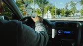painel de instrumentos : The hands of a man on the steering wheel of a car, goes on a typical American suburbs Stock Footage