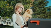 receber : A woman with a dog in her arms picks up letters from the mailbox