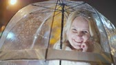 fondo transparente : A middle-aged woman under umbrellas talking on the phone. Snowing