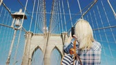 Rear view: A woman is photographed against the backdrop of the Brooklyn Bridge - one of the most popular and recognizable places in New York 動画素材