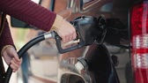 refill : The person closes the tank of the gas tank of the car after refueling
