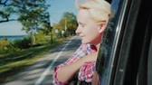 free country : A woman is looking out the window of a traveling car. Enjoy the beautiful scenery, near the forest and the lake. Slow motion video Stock Footage