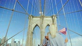 A tourist walks on the Brooklyn Bridge, holds the flag of America in his hand Wideo