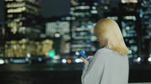 Rear view of Young woman with a smartphone on the background of the lights of a large metropolis Wideo