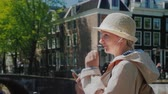 Stylish woman with a smartphone stands on the canal in Amsterdam on the background of old houses