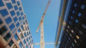 A large tower crane in the downtown of the modern city. Glass office buildings around. Low angle wide shot