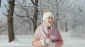 A middle-aged woman is walking in a winter park on a clear day, its snowing 動画素材