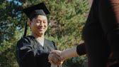 manto : Successful Asian man in graduate clothes accepts congratulations. They shake his hand Vídeos