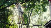 engel : A brave child walks along a tightrope between tall trees. Active childhood and fun Stok Video
