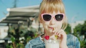 갈증 : Portrait of a funny girl drinking a milkshake at a cafe. Rest with children concept