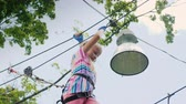 ウォーカー : Low angel view of A brave girl moves along the ropes between the trees, uses a safety rope 動画素材