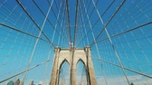 Wide angle shot: Walk on the Brooklyn Bridge. Pylons and ropes of the bridge against the serene blue sky. Pov video 動画素材