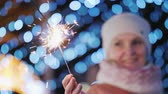 mít : Woman playing with sparkler, her blurry face is visible in the background