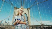 Young woman with a phone in her hand walking along the Brooklyn Bridge in New York