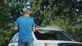 lavagem : A man washes his car in the backyard, rear view