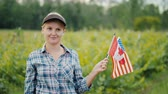 vinificação : Portrait of a farmer with USA and Canada flags in her hand