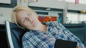 opheffing : Tired passenger sleeps in airport terminal while waiting for his flight