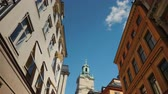 Low angle wide shot to St Nicholas - Storkyrkan bell tower in Stockholm. View through a narrow street with old houses