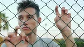 ninhada : Depressed teenager looks over the fence mesh Stock Footage