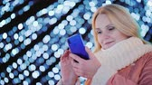 stimmung : Young woman uses smartphone on the background of evening lights of Christmas decorations
