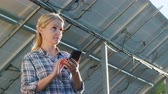 nesil : A woman uses an application to account for the generation of solar panels. It stands at a home solar power plant