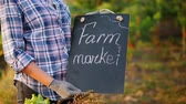 producer : Farmers hands holding a sign. Farmers market near the counter with seasonal vegetables