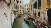 gondole : Venice, Italy, June 2017: Several gondolas with tourists swim in a narrow canal in the center of Venice. The traditional architecture of Venice Filmati Stock