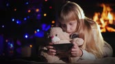 oso de peluche : A child with a teddy bear is playing on a smartphone against the background of a fireplace and a Christmas tree Archivo de Video