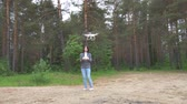 Girl Controls Drone. Girl runs by remote control drone in the woods